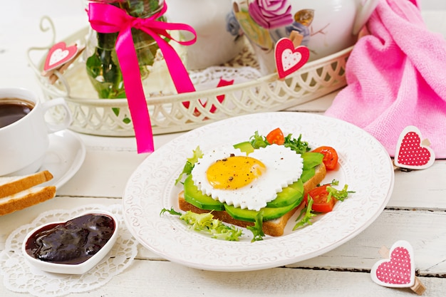 Colazione a san valentino - sandwich di uova fritte a forma di cuore, avocado e verdure fresche. tazza di caffè. colazione inglese.