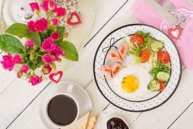 Colazione a san valentino - uovo fritto a forma di cuore, toast, salsiccia e verdure fresche. tazza di caffè. colazione inglese. vista dall'alto