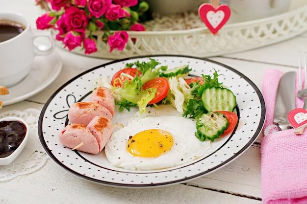 Colazione a san valentino - uovo fritto a forma di cuore, toast, salsiccia e verdure fresche. tazza di caffè. colazione inglese