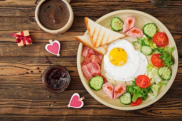 Colazione a san valentino - uovo fritto a forma di cuore, toast, salsiccia, pancetta e verdure fresche. colazione inglese. tazza di caffè. vista dall'alto