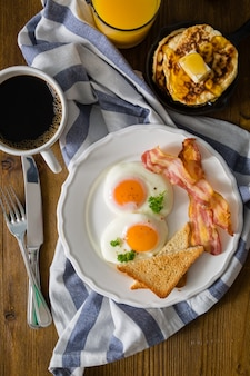 Colazione all'americana con uova, pancetta, toast, pancake, caffè e succo