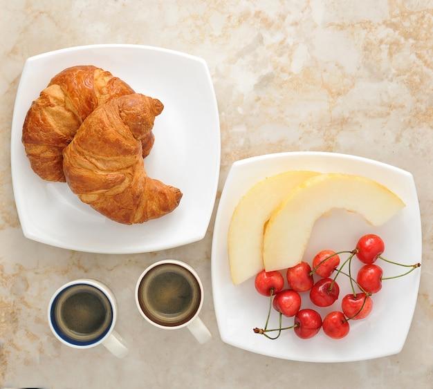 Colazione con caffè, cornetti e frutta - melone, ciliegie
