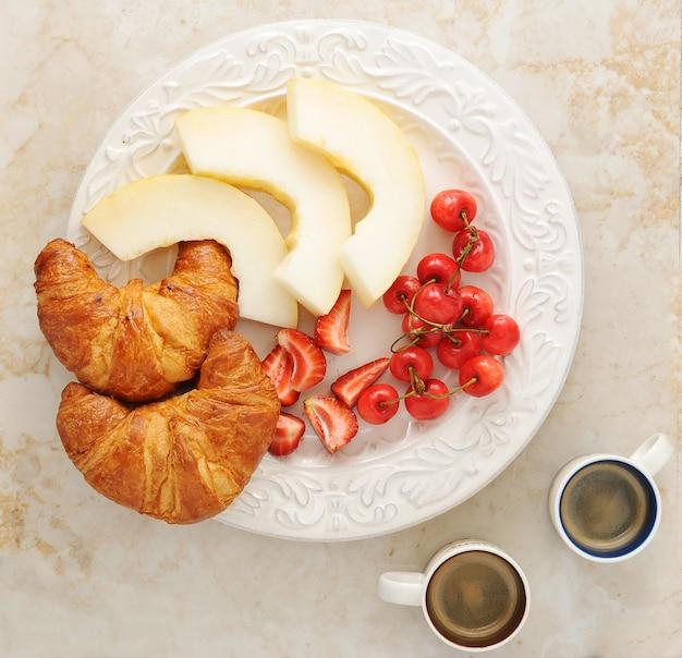 Colazione con caffè, cornetti e frutta - melone, fragole, ciliegie