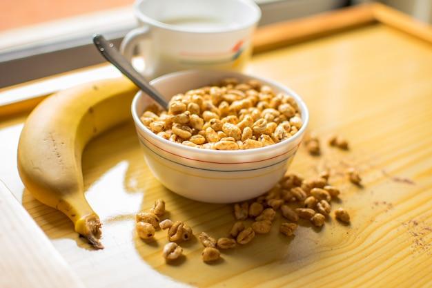 Colazione con cereali in una ciotola con latte, cacao e banana