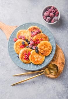 Colazione con cheesecake, frutti di bosco freschi. frittelle di ricotta o frittelle di cagliata. syrniki russo o sirniki