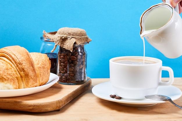 Colazione con cornetti croissant freschi e caffè con latte su uno sfondo blu e tavolo in legno