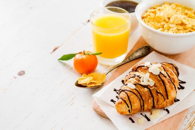 Colazione con croissant, succo di frutta, caffè e cereali