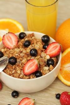 Colazione con frutti di bosco, muesli e succo d'arancia