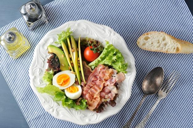 Colazione con pancetta, avocado, uova e insalata