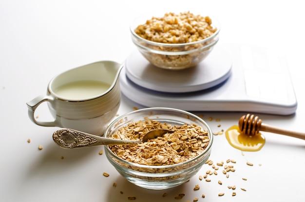 Colazione con porridge di farina d'avena su bilance da cucina digitali, latte e miele su bianco