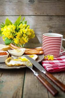 Colazione con salsicce, uova e tazza di tè