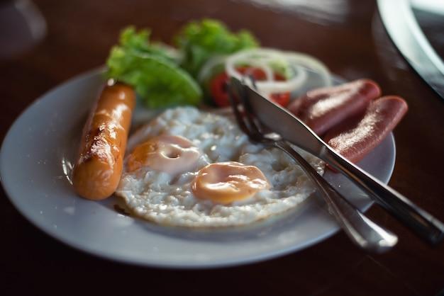 Colazione con uova fritte, pancetta, salsicce
