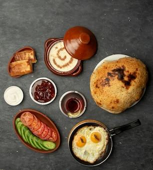 Colazione con uova fritte, porridge, pancake e marmellata
