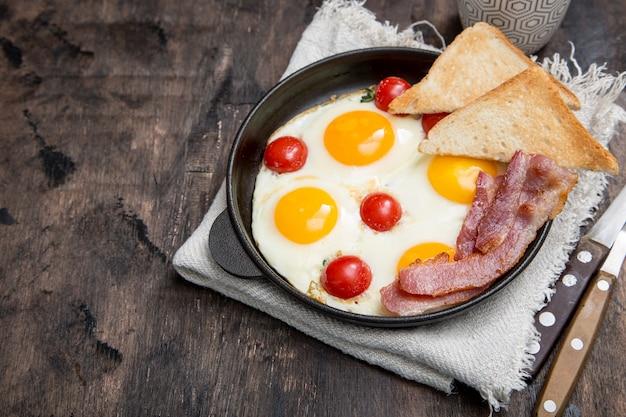 Colazione con uova, pomodorini, pancetta e pane tostato fresco