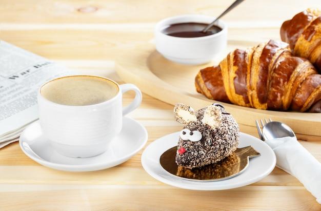 Colazione continentale con cornetti al cioccolato fresco, una torta a forma di topo e caffè. deliziosi pasticcini con caffè espresso.