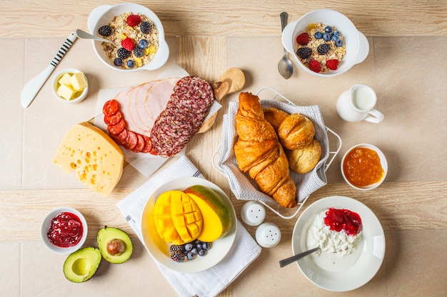 Colazione continentale con croissant, marmellata, prosciutto, formaggio, burro, muesli e frutta.