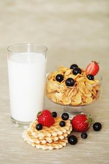 Colazione - cornflakes con un bicchiere di latte. wafer, ribes nero e fragole.