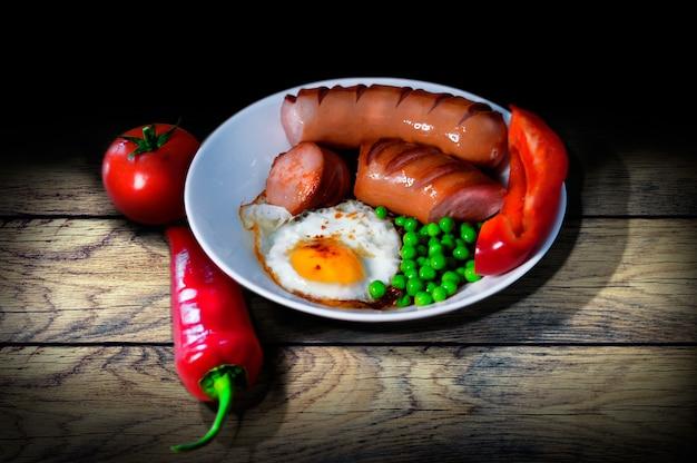 Colazione d'epoca sulla tavola di legno di piselli fritti e piselli salsicce pepe e pomodoro