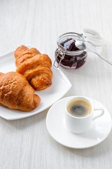 Colazione del mattino caffè, croissant e marmellata su sfondo bianco