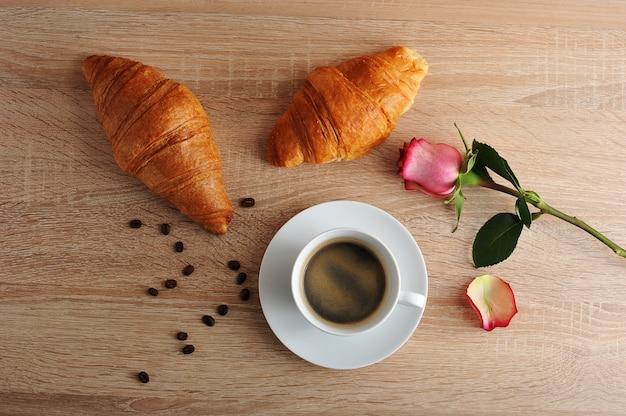 Colazione del mattino - due cornetti, caffè e rosa rossa con petali strappati