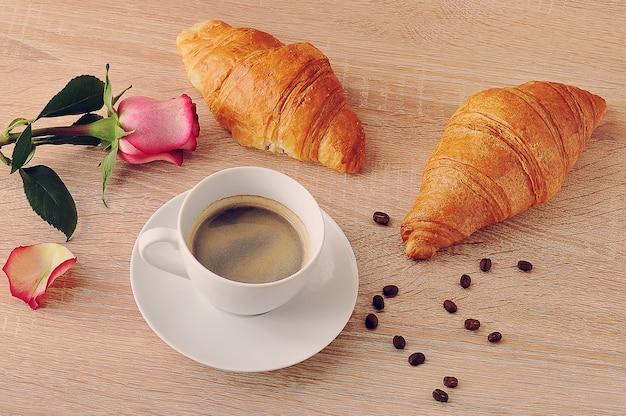 Colazione del mattino - due cornetti, caffè e rosa rossa