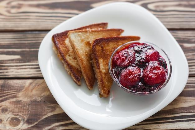 Colazione del mattino toast con fragole e marmellata. pane e confettura. toast caldi freschi con panna. delizioso dessert fatto in casa.