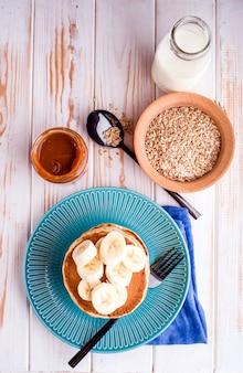 Colazione deliziosa, sana, ricca sul tavolo bianco. uova, farina d'avena, latte, tè, toast alla banana, caramello salato fatto in casa, frittelle con frutta, succo d'arancia. superiore
