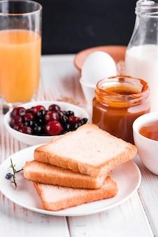 Colazione deliziosa, sana, ricca sul tavolo bianco. uova, farina d'avena, latte, tè, toast alla banana, caramello salato fatto in casa, frittelle con frutta, succo d'arancia.