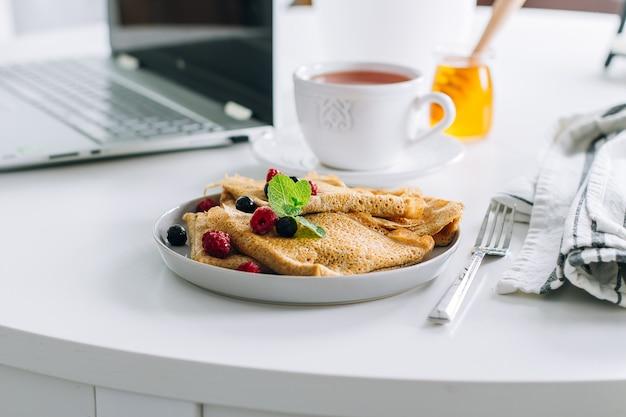 Colazione deliziosa tavolo da pranzo bianco con laptop e crepes fresche, pancake, tazza di tè