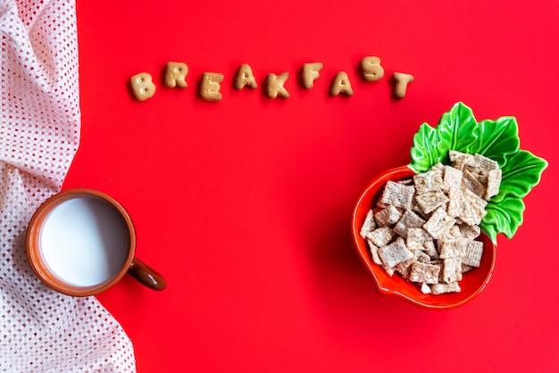 Colazione di cereali cornflakes in ciotola e tazza di latte sul rosso