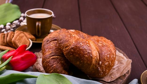 Colazione di pasqua con espresso aromatico fresco, cornetti, uova colorate, tulipani rossi e salice. caffè con pasticcini, fiori su un tavolo di legno. vista dall'alto copia spazio