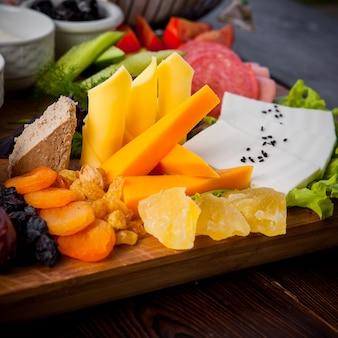 Colazione di primo piano diversi tipi di formaggio, cetrioli, pomodori, lattuga, albicocche secche, uvetta, datteri su un supporto di legno