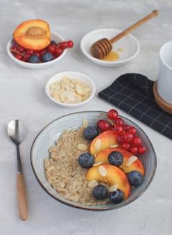 Colazione estiva colazione salutare farina d'avena con pesca, mirtillo, ribes e mandorle calcestruzzo grigio