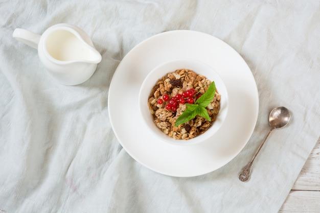 Colazione estiva di muesli, muesli con brocca di latte con decorazione di ribes rosso su tavola di legno chiaro. vista dall'alto.