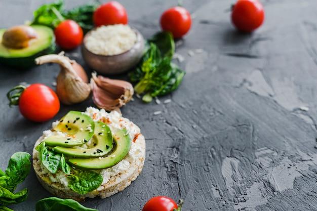 Colazione fatta in casa con pomodorini; aglio; avocado e riso crudo su sfondo