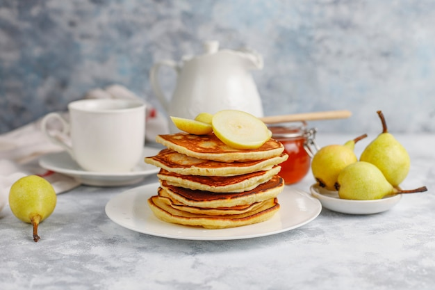 Colazione fatta in casa: frittelle all'americana servite con pere e miele con una tazza di tè sul cemento. vista dall'alto e copia