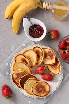 Colazione fatta in casa frittelle con marmellata di bacche, miele, banane e fragole sul tovagliolo grigio su sfondo concreto