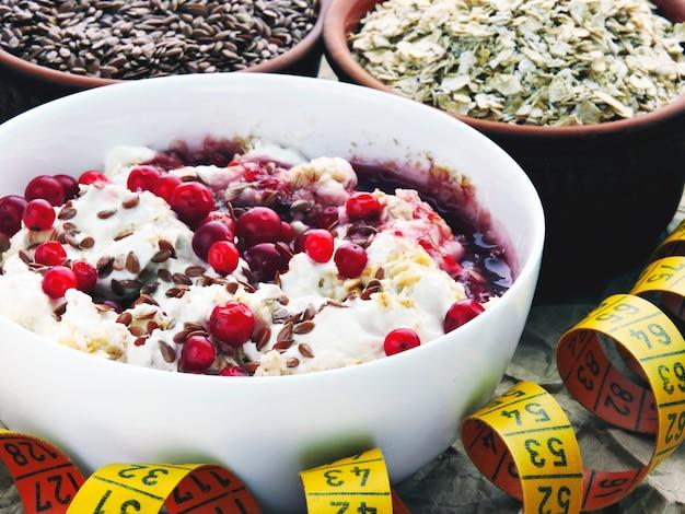 Colazione fiocchi d'avena con yogurt, mirtilli rossi e semi di lino. nastro di misurazione, fiocchi d'avena, semi di lino. spuntino fitness. il concetto di colazione per dimagrire.