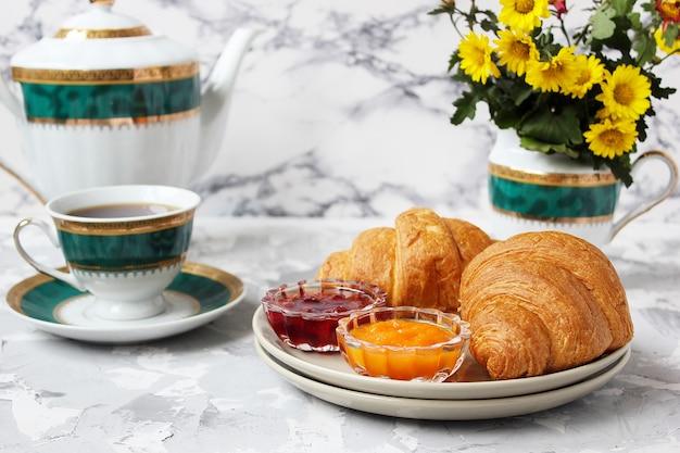 Colazione francese con cornetti, marmellata di albicocche, marmellata di ciliegie e una tazza di tè, fiori rossi e gialli