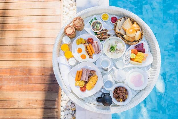 Colazione galleggiante impostata nel vassoio con frittata di uova fritte salsiccia pane pane frutta latte succo di caffè