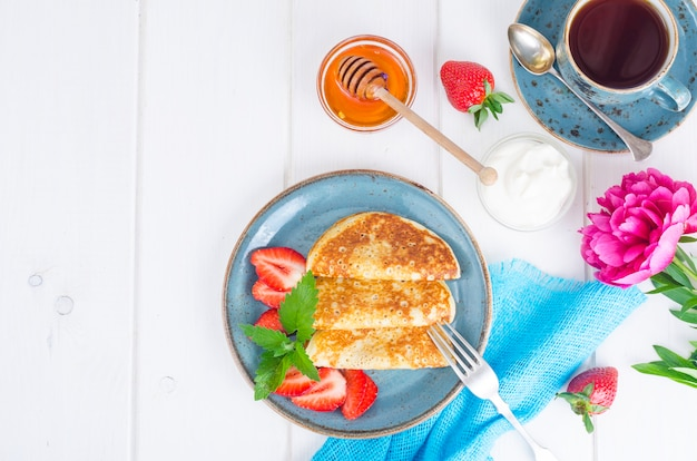 Colazione gourmet. pancake fritti dolci deliziosi con le fragole fresche.