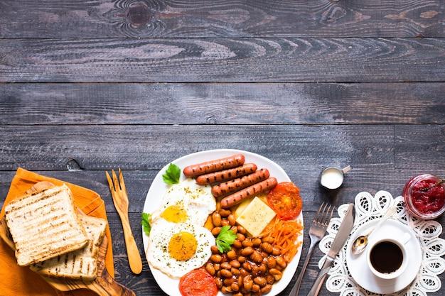 Colazione inglese. uova fritte, salsicce, fagioli, toast di pane, pomodori, formaggio su uno sfondo di legno,
