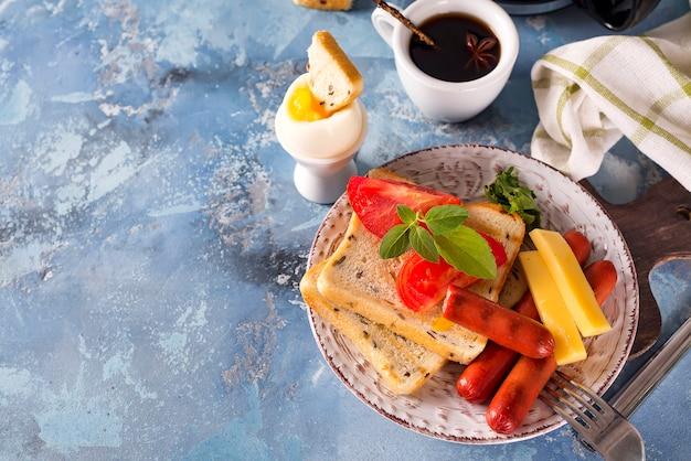 Colazione inglese. uova fritte, salsicce, toast, pomodori sul tavolo di pietra.