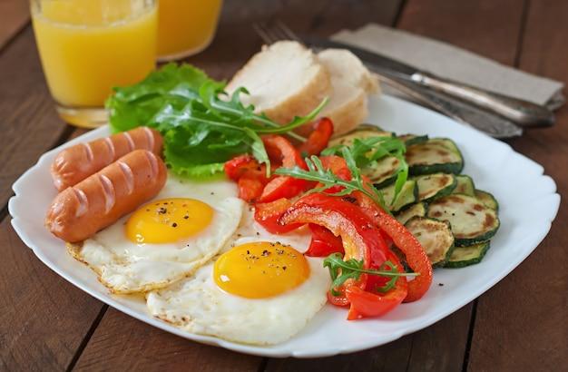 Colazione inglese - uova fritte, salsicce, zucchine e peperoni dolci