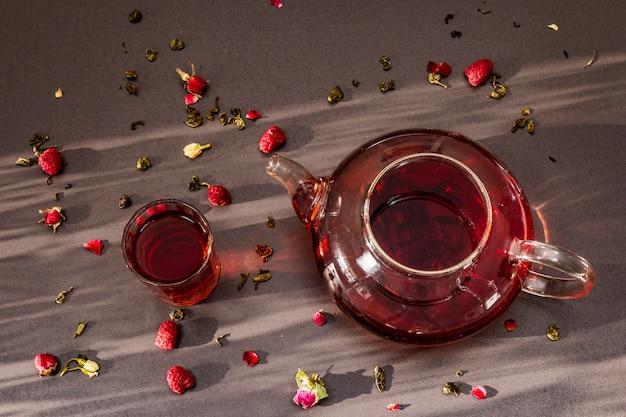 Colazione mattutina soleggiata. tè verde lampone dolce in bollitore di vetro con frutta secca, fiori e foglie