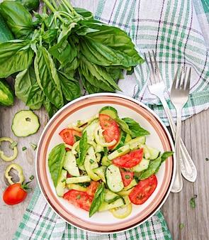 Colazione nel giardino estivo. insalata di pomodori e cetrioli con cipolle verdi e basilico.