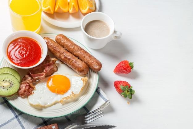 Colazione nutriente, fragola, pane, succo d'arancia di caffè, salsiccia, uovo