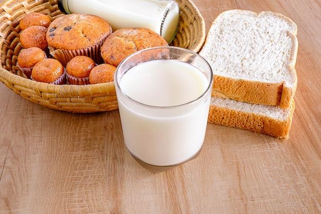Colazione, pane in un cestino e bicchiere di latte sul tavolo.