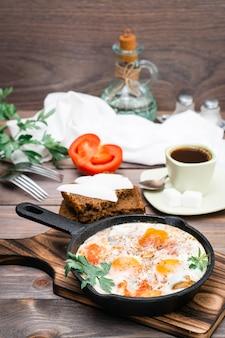 Colazione pronta: shakshuka di uova fritte con pomodori e prezzemolo in padella, pane con burro e caffè su un tavolo di legno