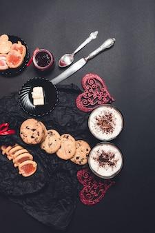 Colazione romantica. due tazze di caffè, cappuccino con biscotti al cioccolato e biscotti vicino a cuori rossi su sfondo nero tavolo. giorno di san valentino. amore. vista dall'alto.